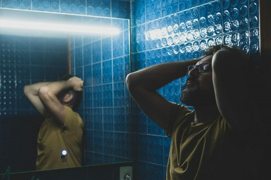 close up ad portrait of sad and depressed man upset in the bathroom in front of the mirror