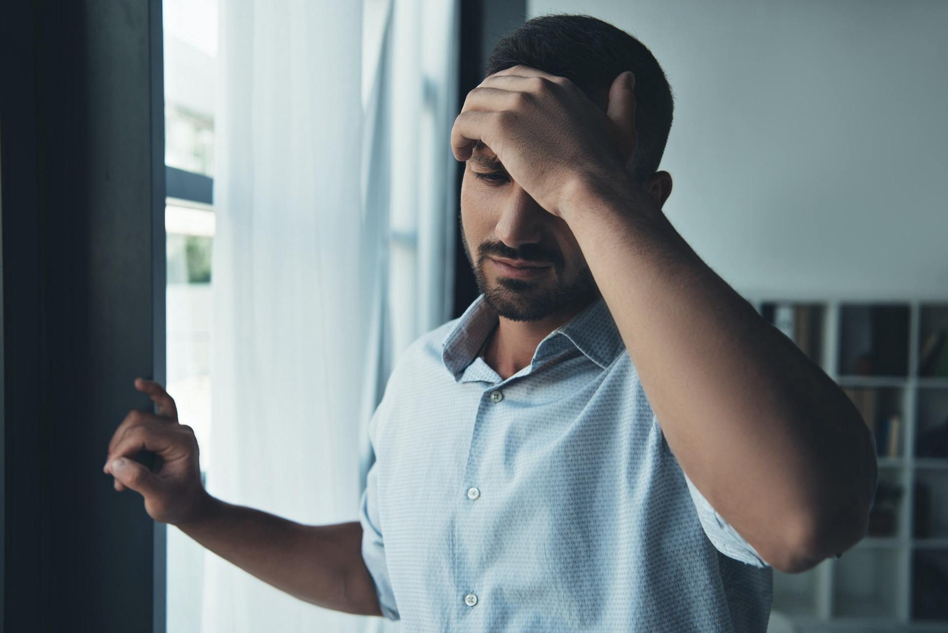 upset man suffering from headache at home