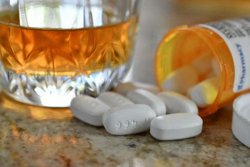 Warning, Danger - Never mix drugs and alcohol - a bottle of pills next to a shot of liquor.