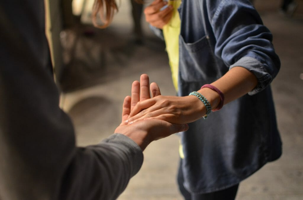 man and woman holding hands on street